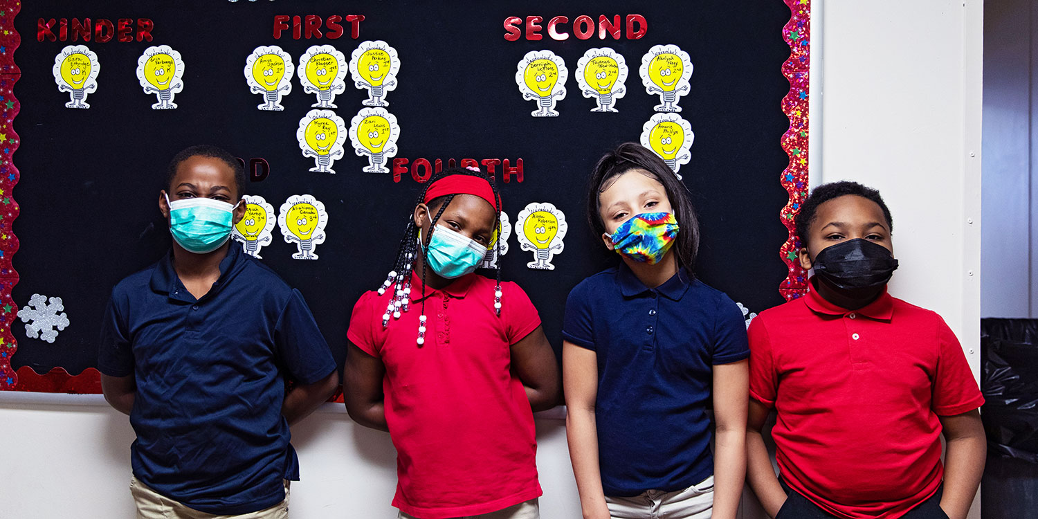 Students standing in front of a bulletin board.