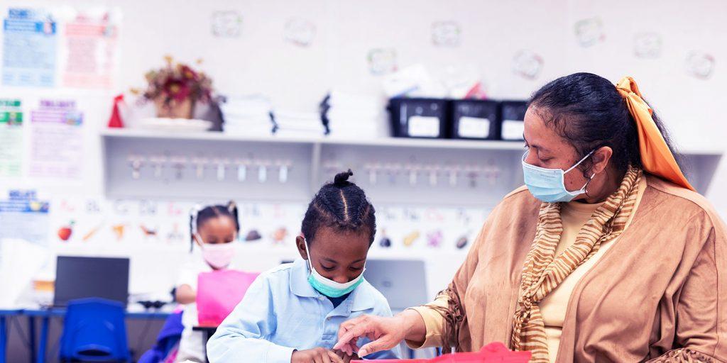 Teacher helping elementary student at a desk.