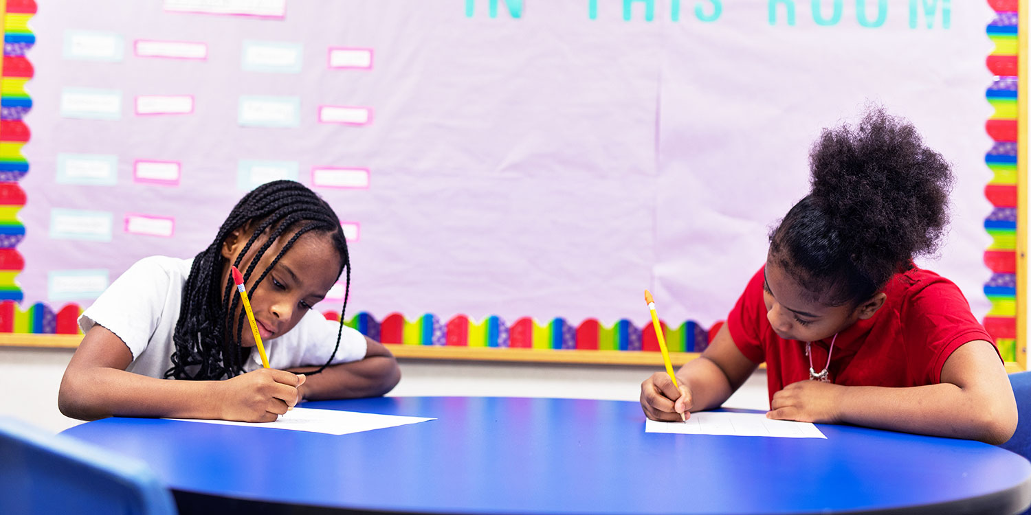 Students writing at a desk.
