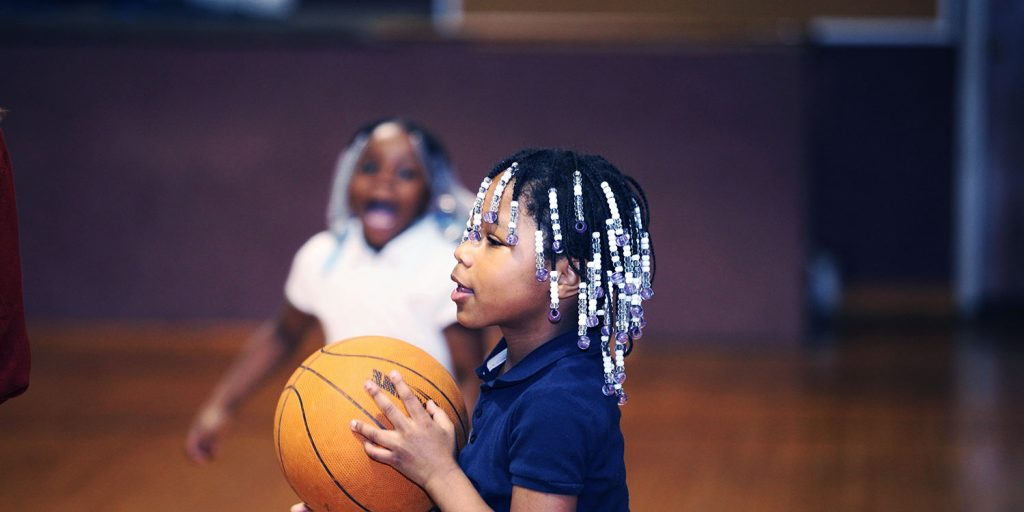 Elementary student holding a basketball in the school gym.