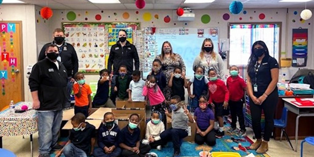Amazon Business Team and Ms. Reno's kindergarten class receiving donated classroom items.